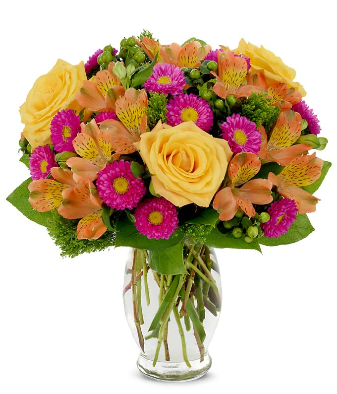 Spring bouquet with hot pink asters, yellow roses and green hypericum