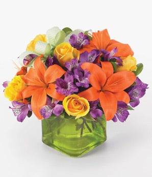 Orange lilies, yellow roses and purple alstroemeria in a square glass vase