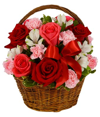 Pink roses, red roses and pink carnations in a woven basket