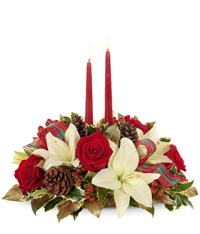 Flowers - Home for the Holidays Centerpiece - Regular Asiatic lilies, roses, hypericum and carnations are blended creatively in an oval bowl container with pine cones, a plaid ribbon and two Patrician tapered candles to form an absolutely stunning holiday centerpiece that will welcome home loved ones and friends while artfully capturing the many joys of the Christmas season. Measures 6 H X 10 L. Details:  White Asiatic Lilies  Red Roses  Red Hypericum Berries  Red Carnations  Two Red Candles