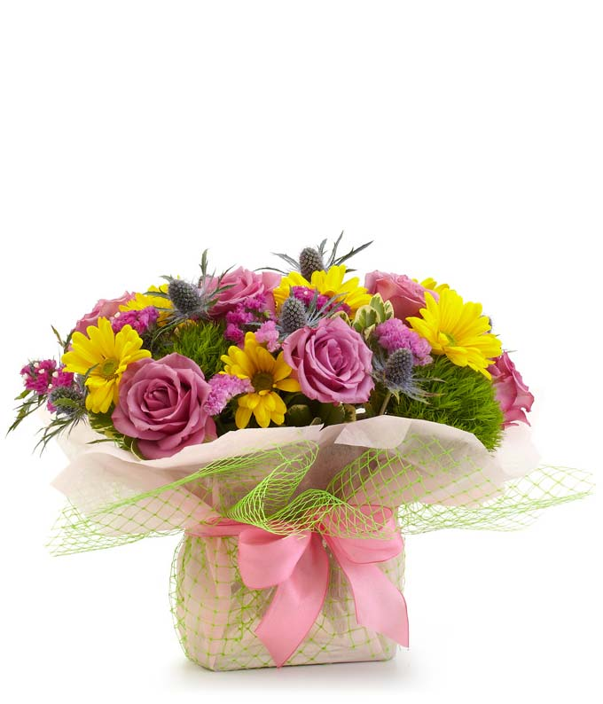 Purple Rose & Daisy Garden - Regular Express just the right sentiment, straight from the heart, with this sumptuous arrangement of eryngium, daisy poms, roses, trachelium and statice in a clear rectangular glass vase enhanced by light pink deco wrap, green mesh and a beautiful pink ribbon. Measures 11 H by 12 L. Includes:  Purple Roses  Yellow Eryngium  Yellow Daisies  Clear Vase Decorated with Ribbon