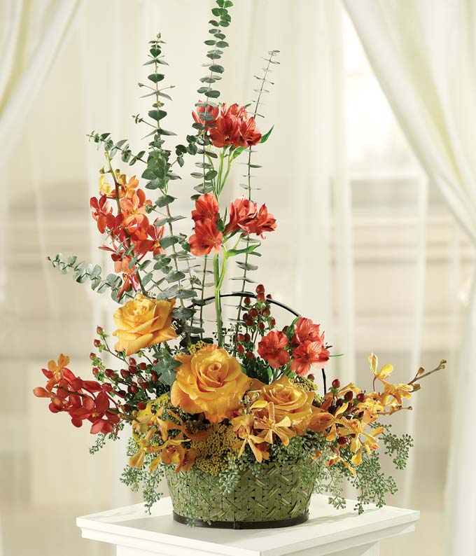 Tribute basket with yellow roses, red alstroemeria and orchids