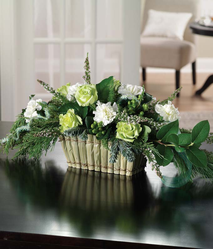 Centerpiece of green roses, hypericum and cream carnations