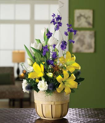 Yellow lilies and white tulips in a get well flower basket