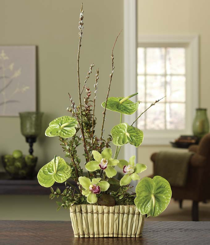 Green orchids and huckleberry in a woven basket
