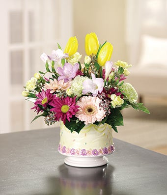 birthday arrangement with yellow tulips, pink daisies and green carnations