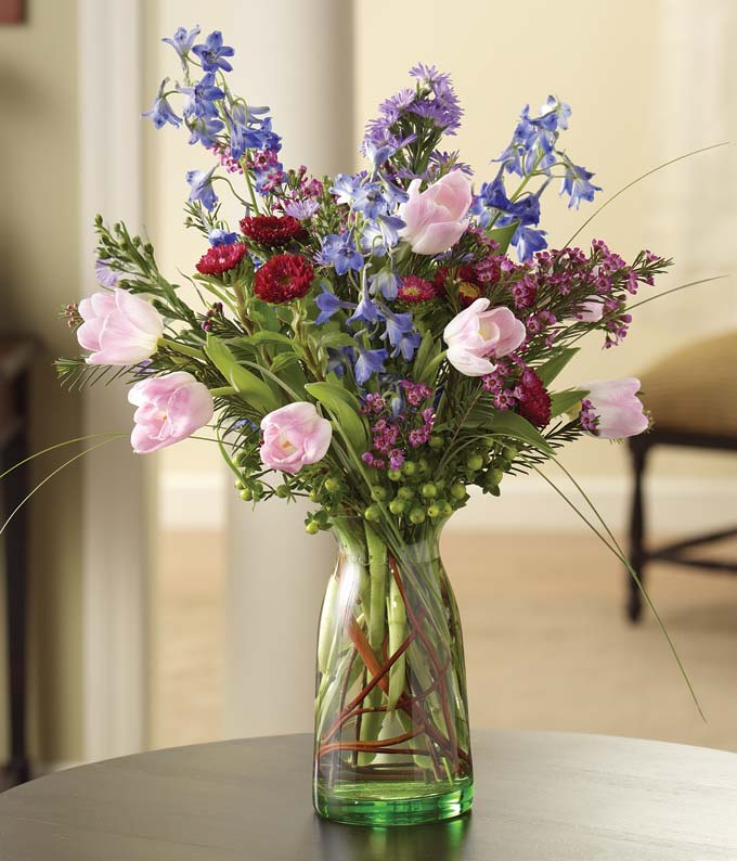 Pink Tulips and blue delphinium in a milk jar