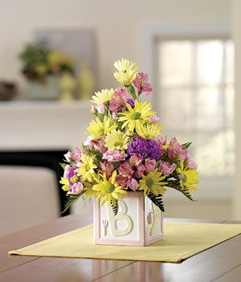 Pink daisies, pink alstroemeria in new baby girl vase