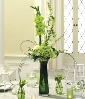 Green & white roses and orchids in a centerpiece