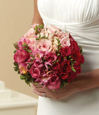 Red roses and hot pink roses in a bridal bouquet for delivery