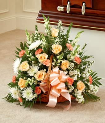 Peach, orange and white flowers in a sympathy basket