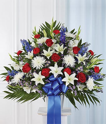 Red roses, white lilies and white mums in a sympathy basket