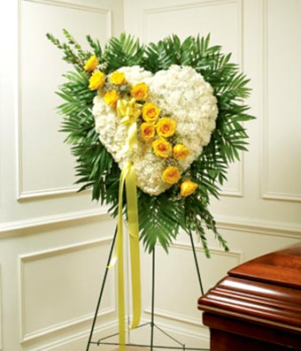 White flowers and yellow flowers in heart shaped standing spray