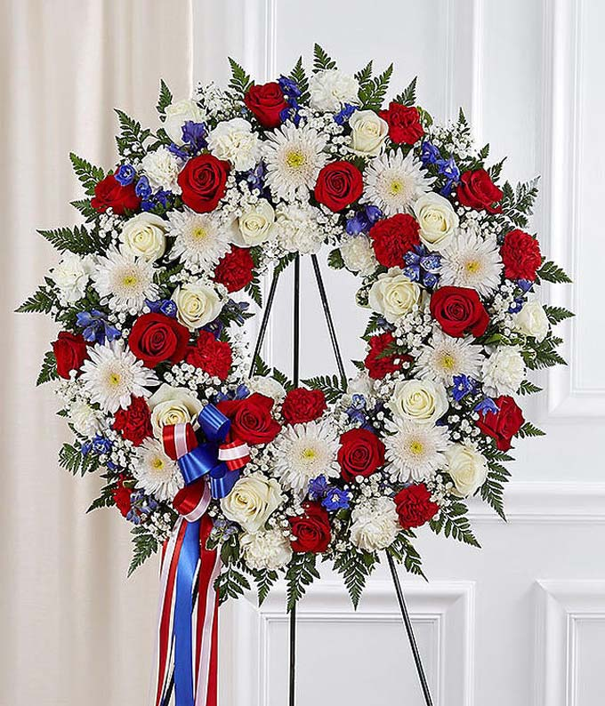 Red roses, white carnations and blue delphinium in funeral wreath
