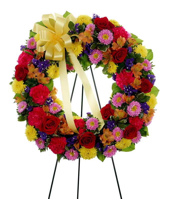 Sympathy wreath of red roses, pink carnations and yellow mums