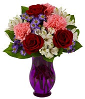 Red roses, pink carnations and white alstroemeria in a purple vase