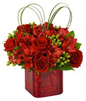 Red roses and alstroemeria in a red vase