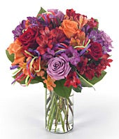 Purple roses, orange roses, red roses and alstroemeria in glass vase