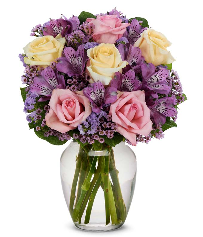 pink roses, yellow roses and purple alstroemeria in a clear glass vase