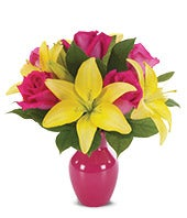 Yellow lilies and pink roses in a pink vase