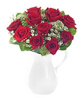 Red roses and white wax flower in reusable pitcher