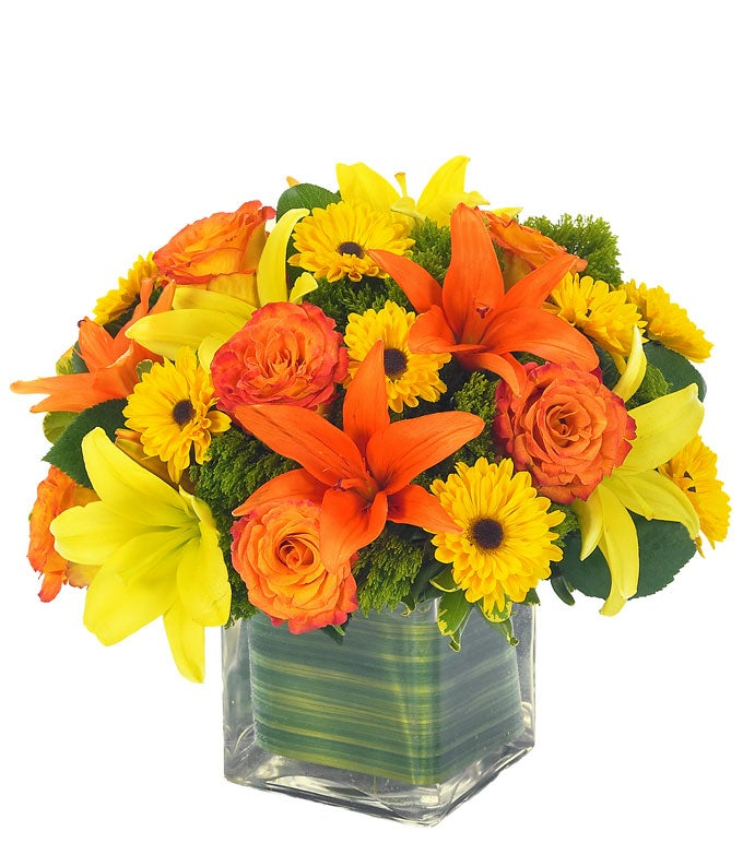 Yellow lilies, orange lilies and orange roses in rectangle vase