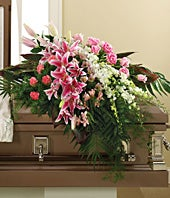 Pink stargazer lilies, white orchids and pink carnations in a casket spray