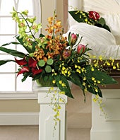Funeral pedestal arrangement with green, red and orange flowers