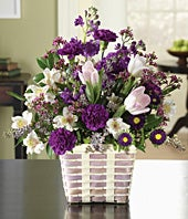 Purple carnations, white alstroemeria and pink tulips in a basket