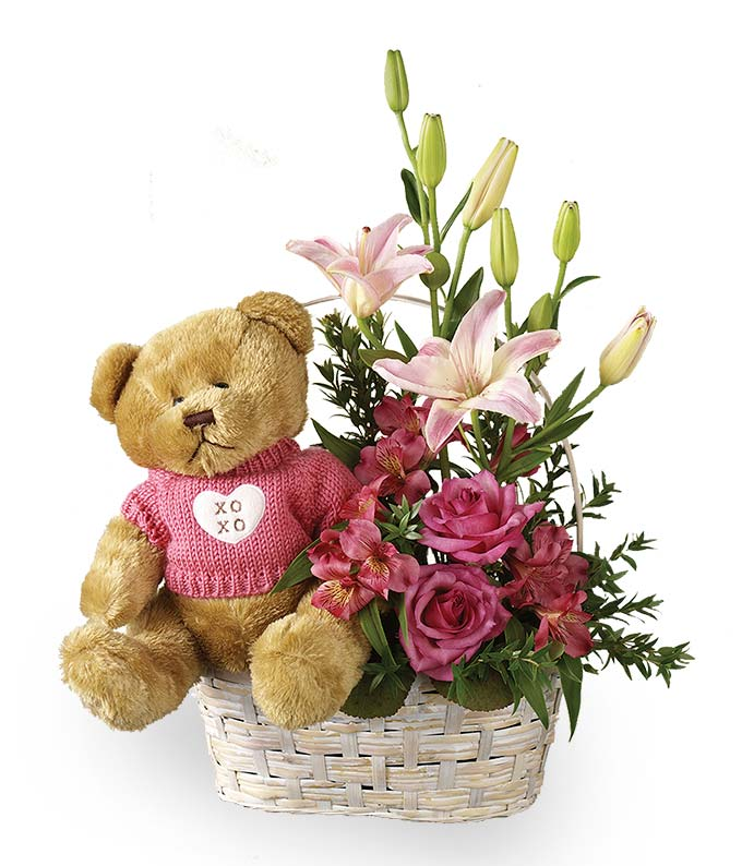 Pink roses and lilies with teddy bear in basket