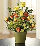 Yellow roses, orange spray roses and tulips in a basket