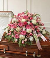 Pink roes, pink gerbera daisies and white flowers in a casket cover