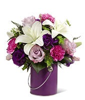 Yellow lilies and purple flowers in a purple vase