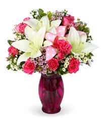 Pink roses with white lilies in a pink vase