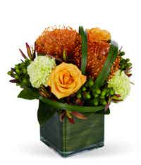 Orange and green floral bouquet in a square vase