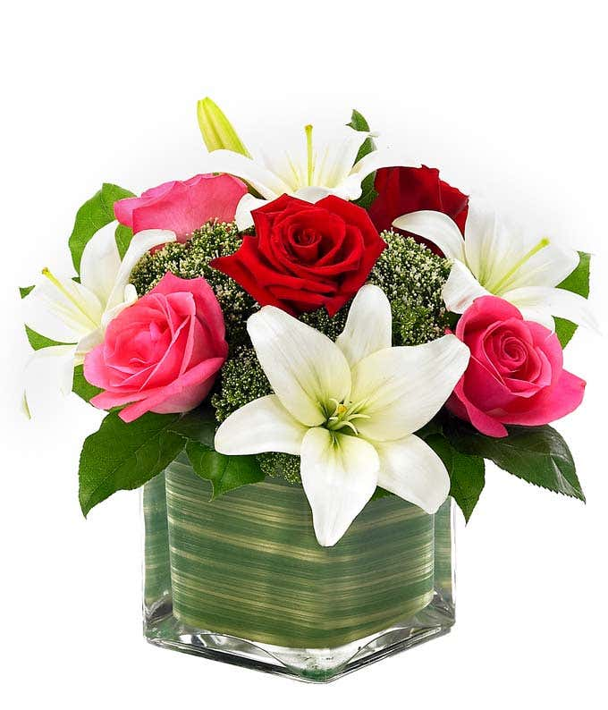 Pink roses, red roses and white lilies in square vase