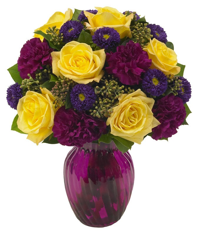 Purple carnations, purple asters and yellow roses in a purple vase