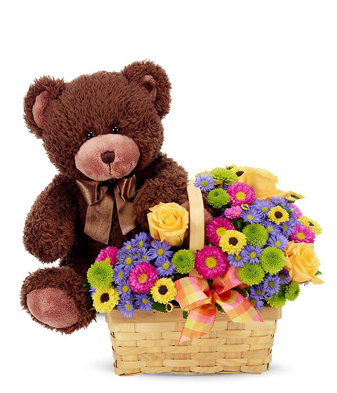 Plush teddy bear delivered inside a basket of flowers