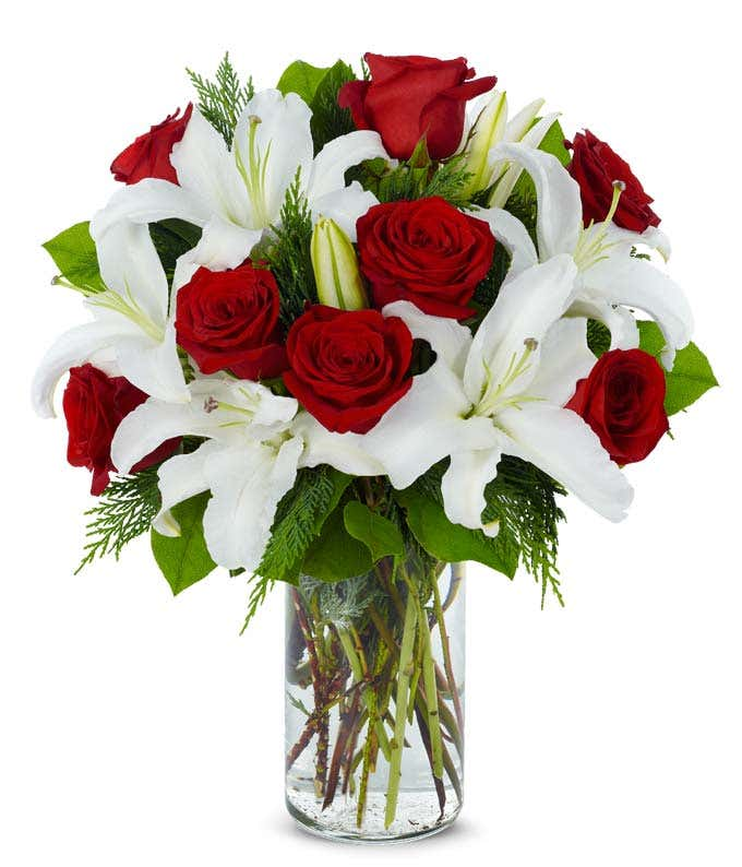 Long stem red roses arranged with white lilies in glass vase