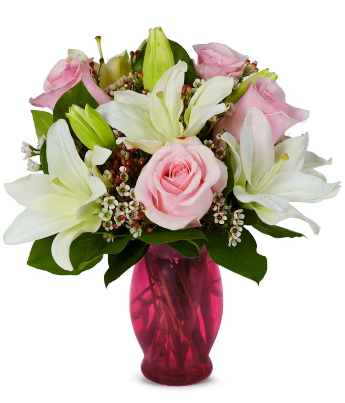Light pink roses, white waxflowers and white lilies in a pink vase