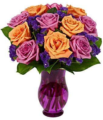 Purple roses arranged with orange roses in a purple vase
