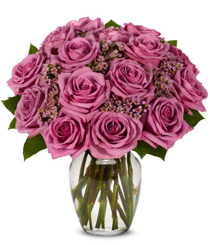 Purple rose arrangement with purple decoration in a glass vase