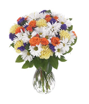 White daisies, orange roses and carnations in a vase