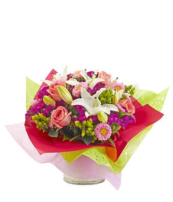 Pink lilies, white lilies and hypericum in Mother's Day arrangement