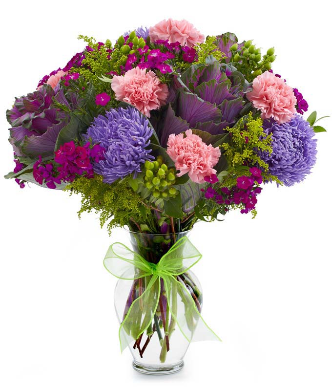 Pink carnations, purple kale and asters in glass vase with bow