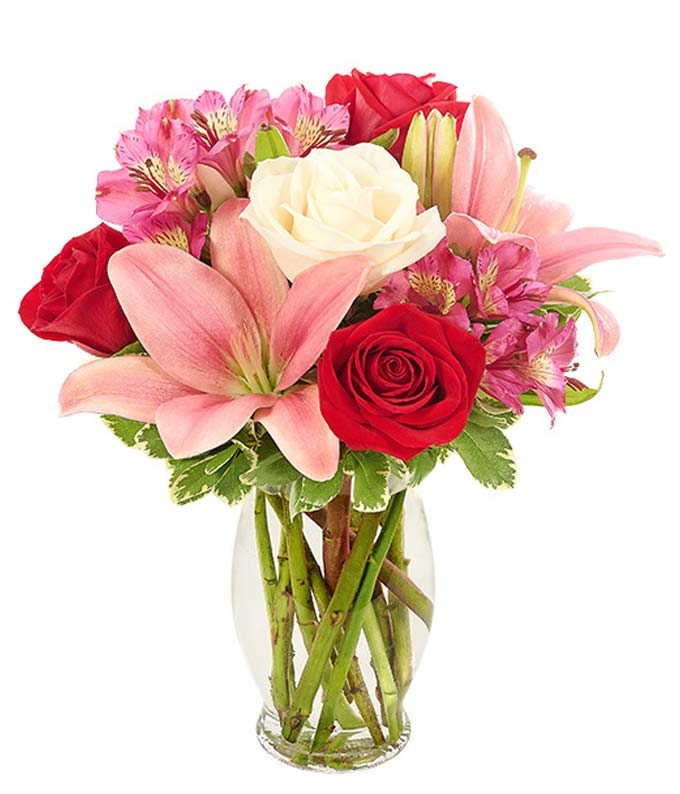 Cute romantic flower arrangement with red roses, pink lilies and white lilies