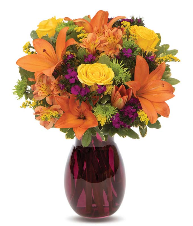 Orange lilies, yellow roses and purple flowers in a fall-colored vase