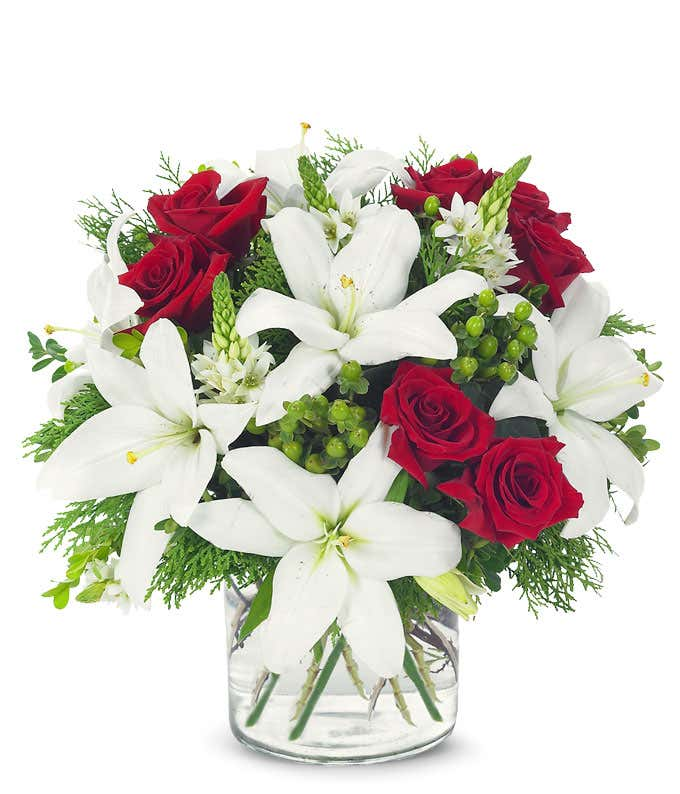 Red roses, white lilies and hypericum in circular glass vase