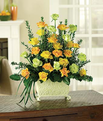 Yellow roses, orange roses and green roses in a unique planter
