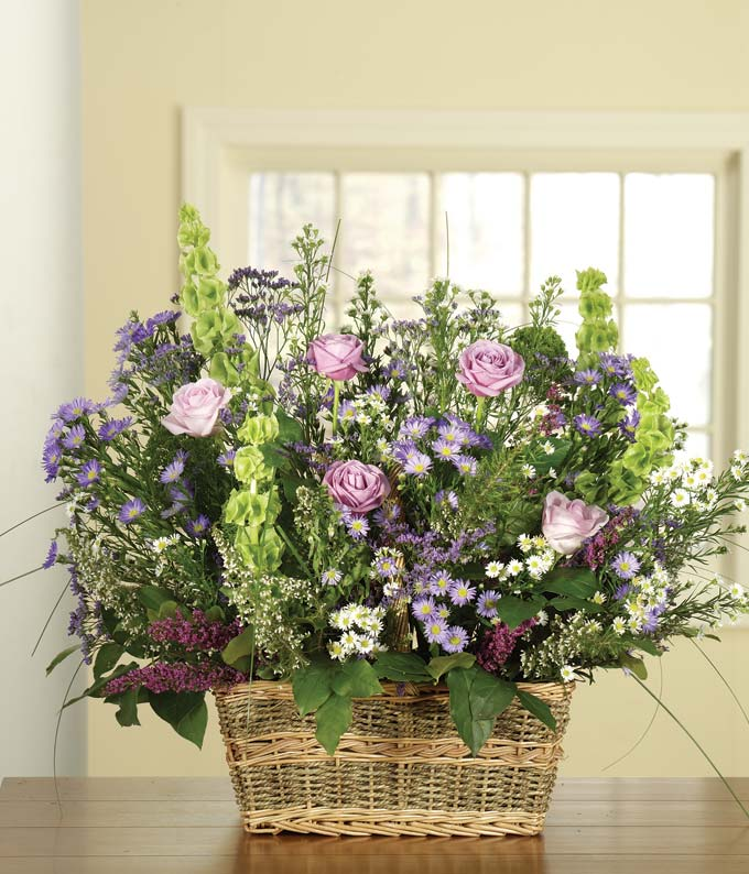 Sympathy arrangement with white roses, purple roses and bells of ireland